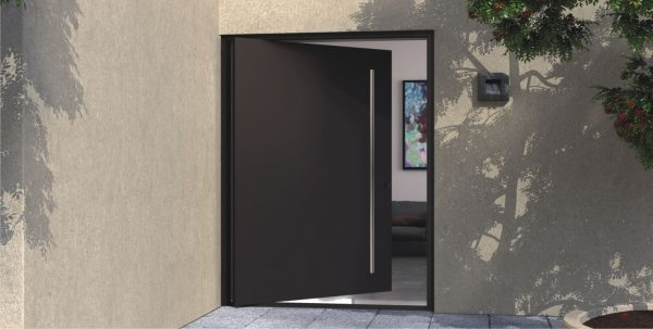 black metal pivot front door with round stainless steel door pull in front of modern home