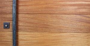 mahogany wood behind round modern door pulls and black baldwin square lock