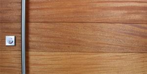 genuine mahogany wood door behind round brushed stainless steel door handles and matching stainless steel square door lock