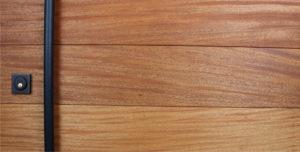 mahogany hardwood front door with round black powder-coated door handles and matching baldwin black lock