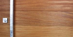 mahogany wooden door behind serrated and polished modern door pulls with stainless steel door lock