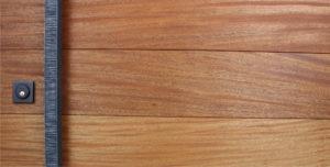 mahogany hardwood door behind hand-serrated square custom door handles and black square door lock