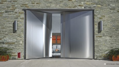 large double pivot front doors made of brushed stainless steel with long round stainless door hardware