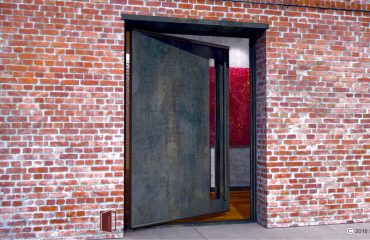 raw steel single pivot door with transparent door lite and round matching steel door pulls