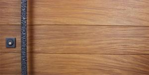 teak wooden door behind round hammered door pulls and black square baldwin door lock