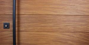teak genuine wood door behind round black powder-coated door handle and square black door lock