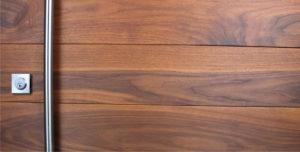 real walnut wood front door behind round stainless steel door pulls and baldwin square stainless steel door lock