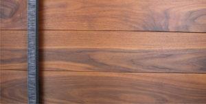 contemporary wooden front door made of walnut hardwood and serrated square door handles