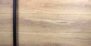 white oak hardwood door behind round black powder-coated door hardware