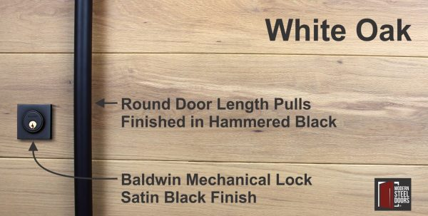round black door hardware with matching black baldwin lock in front of white oak wood