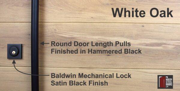 round black door hardware with matching black baldwin lock in front of white oak wood
