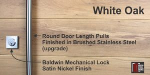 white oak wood behind round stainless steel door handles and stainless steel baldwin lock