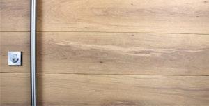 white oak hardwood behind stainless steel round door handle and stainless steel square door lock