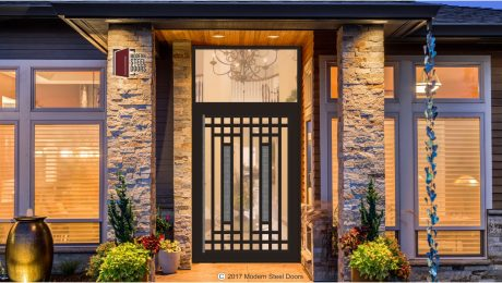transitional front door design made of glass and metal with hand sculpted serrated highlighted centerpieces and transom